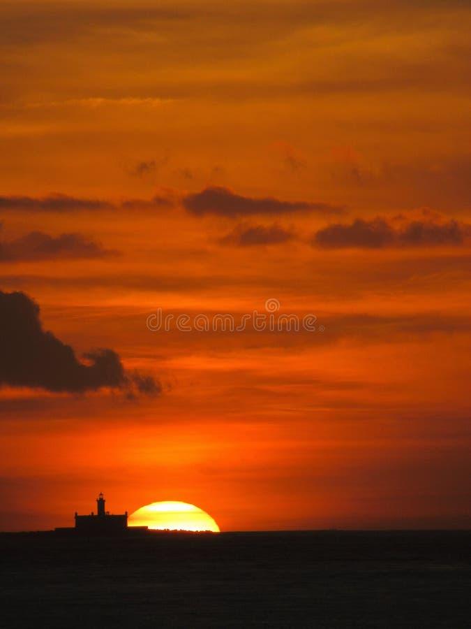 Fyr på solnedgången: Djup orange himmel royaltyfri fotografi