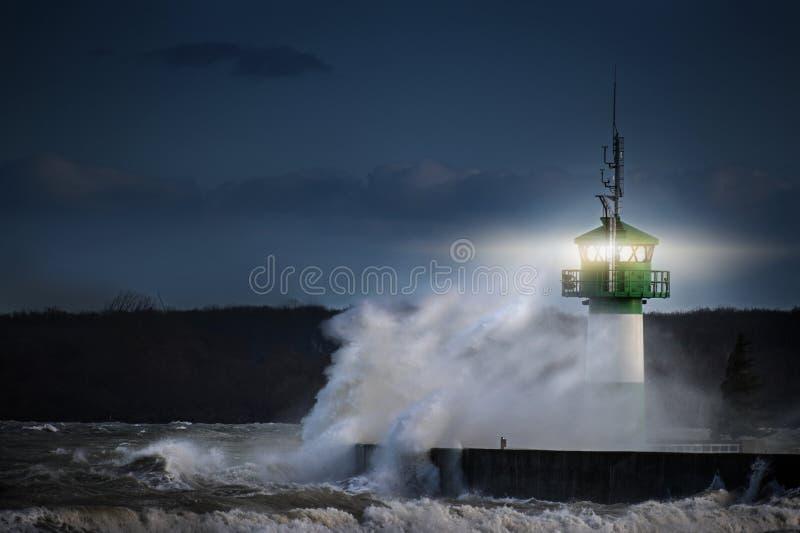 Fyr under storm, i att plaska sprej på natten på Östersjön, Travemuende i den Luebeck fjärden, kopieringsutrymme royaltyfri bild