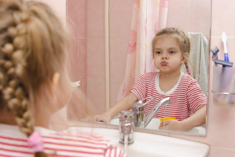 Fyraåringflickan sköljer tänder, når han har gjort ren i badrummet arkivbild