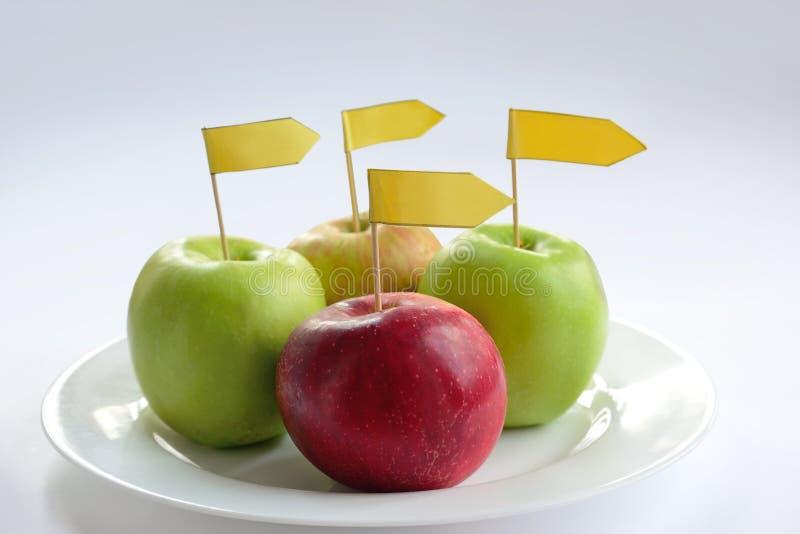 Fyra äpplen med etiketten royaltyfria foton