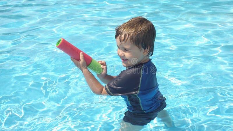 Fyra år gammal unge som spelar i simbassängen arkivfoto