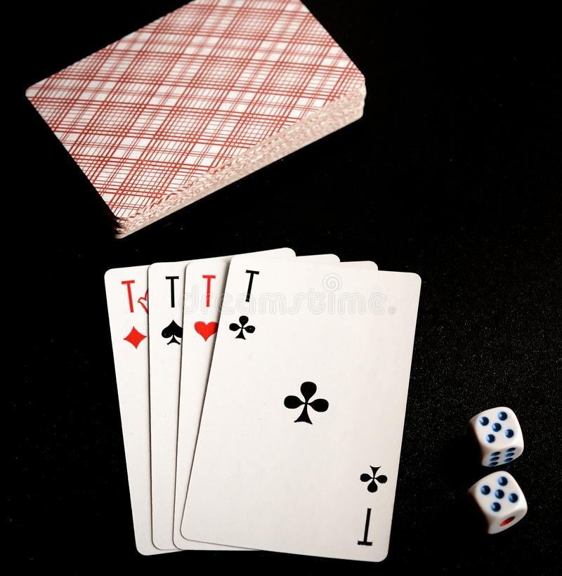 Fyra överdängare och två tärning med att spela kort på den svarta bakgrunden arkivfoton