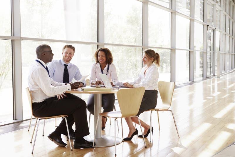 Fyra affärskollegor i ett lagmöte, full längd royaltyfria bilder