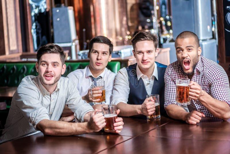 Fyra affärsmän dricker öl och jublar och ropar tillsammans klockan royaltyfri bild