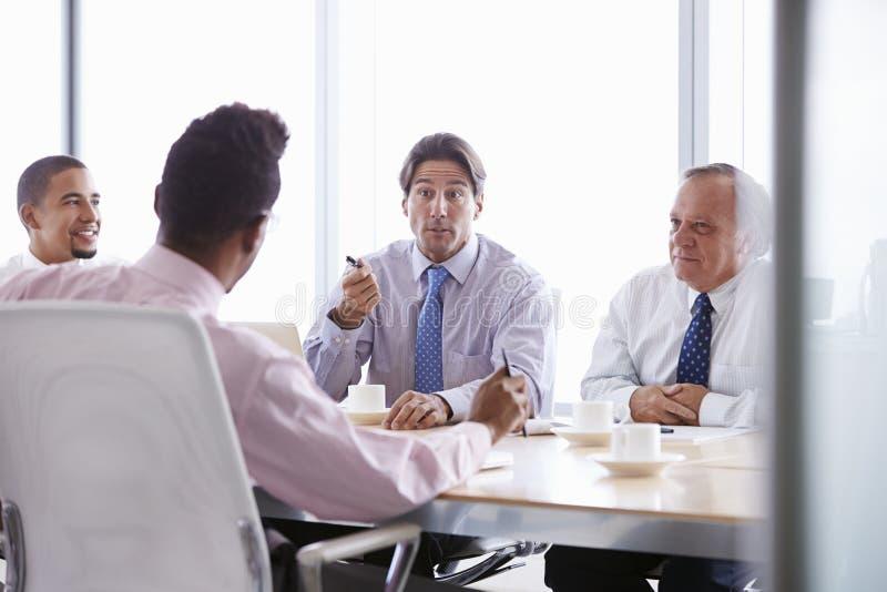 Fyra affärsmän som har möte runt om styrelsetabellen arkivbilder