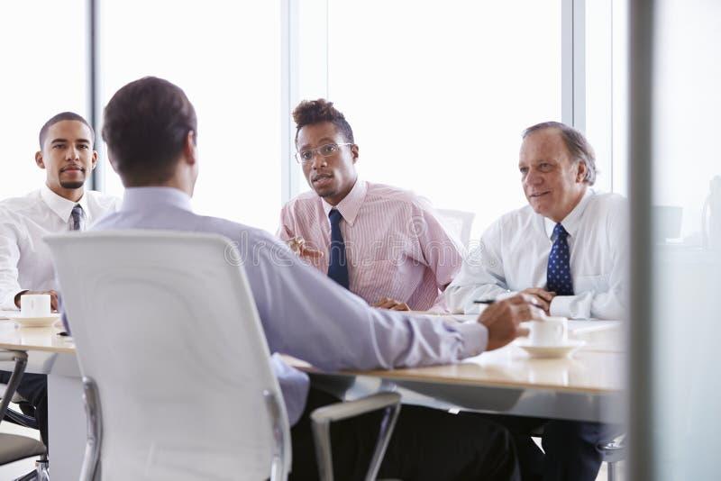 Fyra affärsmän som har möte runt om styrelsetabellen fotografering för bildbyråer