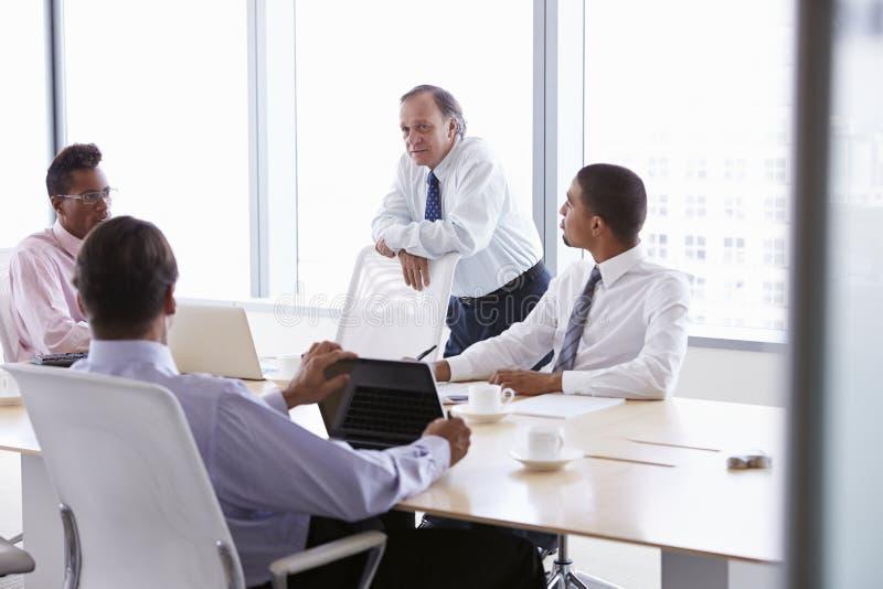 Fyra affärsmän som har möte runt om styrelsetabellen royaltyfri foto