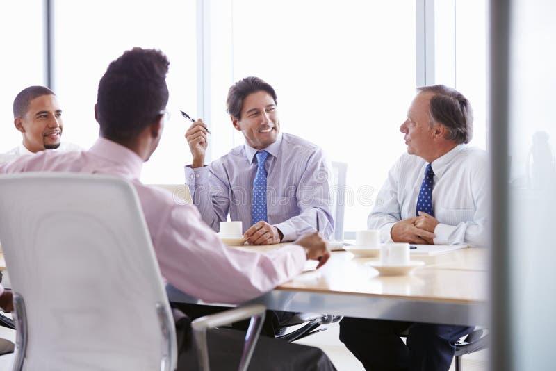 Fyra affärsmän som har möte runt om styrelsetabellen arkivbild