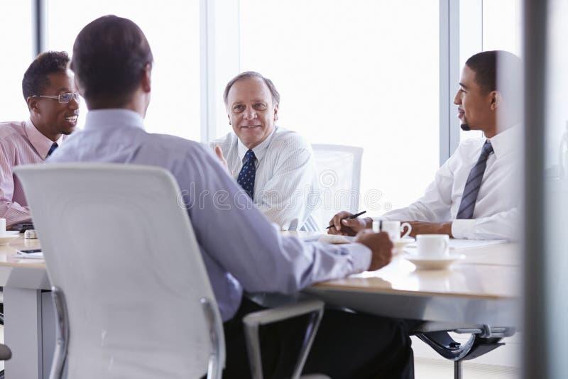 Fyra affärsmän som har möte runt om styrelsetabellen arkivfoto