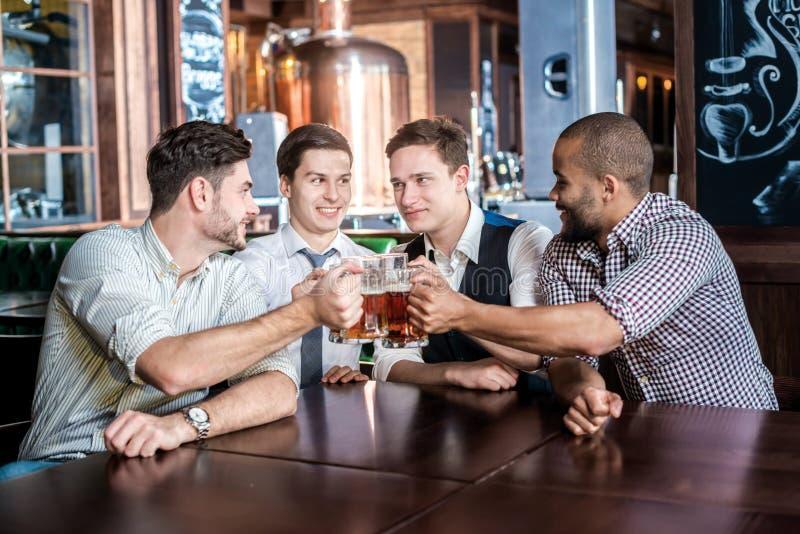 Fyra affärsmanvänner dricker öl och spenderar tid tillsammans i a arkivfoton