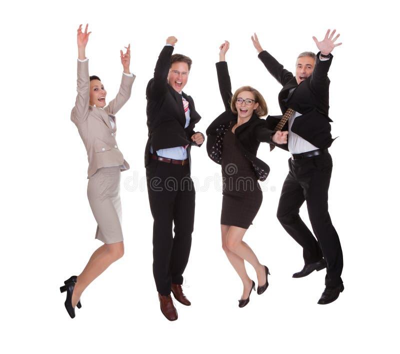 Fyra affärspartners som hoppar för glädje arkivfoton