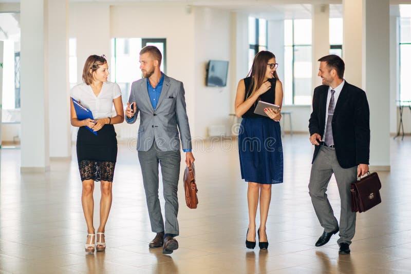 Fyra affärspersoner som i regeringsställning talar och går lobbyen fotografering för bildbyråer