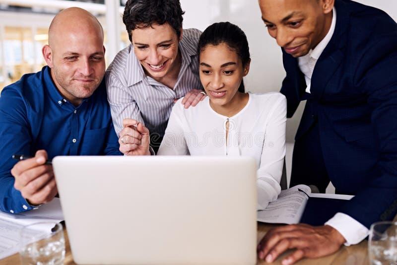 Fyra affärspersoner som ler om deras utövande bonusar som, blir partner med royaltyfria bilder