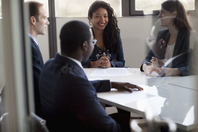 Fyra affärspersoner som sitter och diskuterar på ett affärsmöte arkivfoto