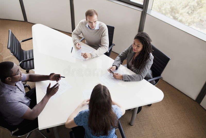 Fyra affärspersoner som sitter på en konferenstabell och diskuterar under ett affärsmöte royaltyfri fotografi