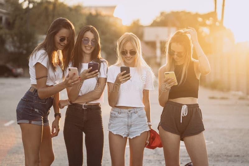 Fyra attraktiva kvinnor står på bilparkering med smartphones arkivbilder