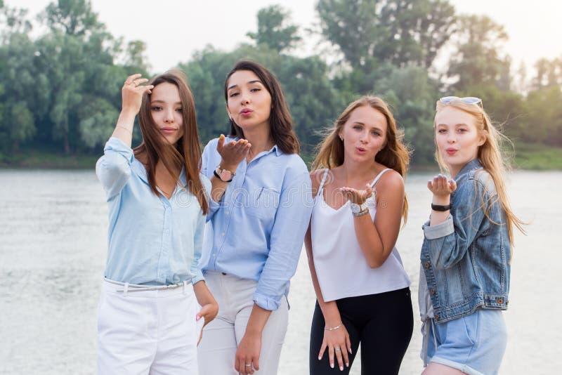 Fyra attraktiva unga kvinnor som står och överför kyssar på den utomhus- kameran träd och flod på bakgrund arkivfoto