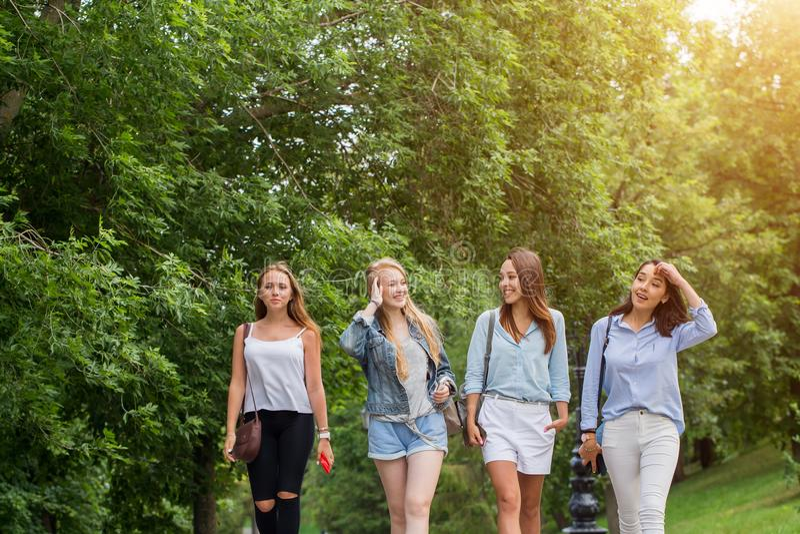 Fyra attraktiva unga kvinnor som talar att gå tillsammans royaltyfria foton