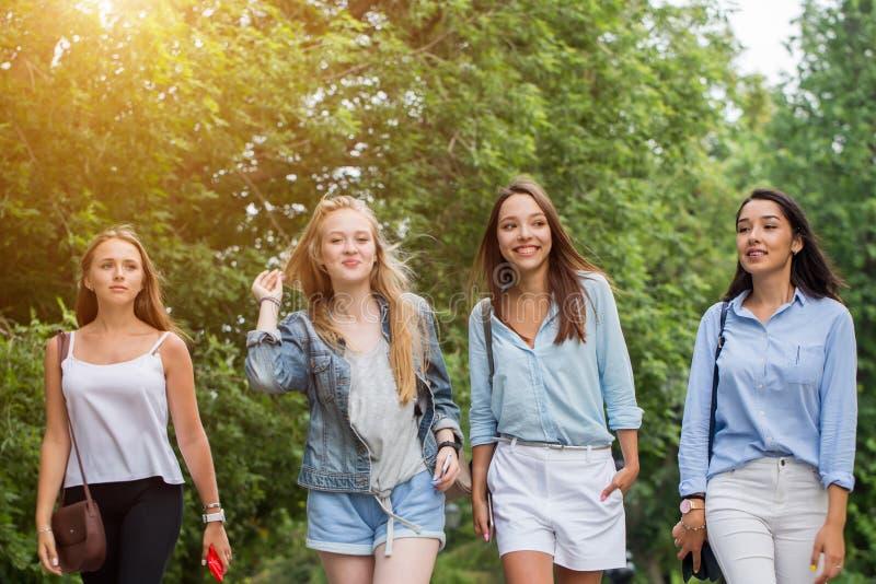 Fyra attraktiva unga kvinnor som talar att gå tillsammans royaltyfri bild