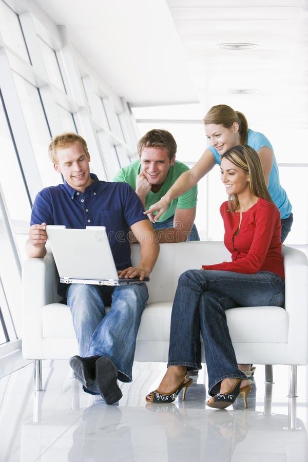 fyra bärbar datorlobbyfolk som pekar att le arkivbilder