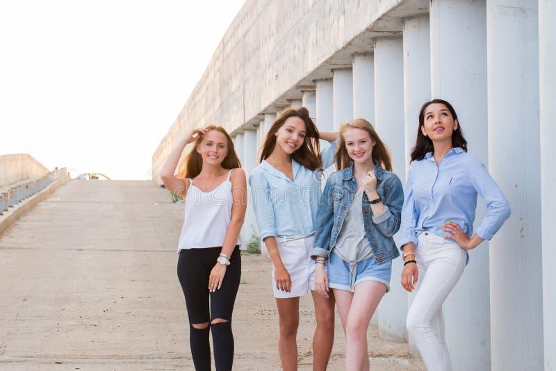 Fyra bästa flickvänner som tillsammans ser kameran folk livsstil, kamratskap, kallbegrepp royaltyfria bilder