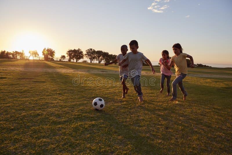 Fyra barn som jagar en boll under en lek i ett fält arkivfoto