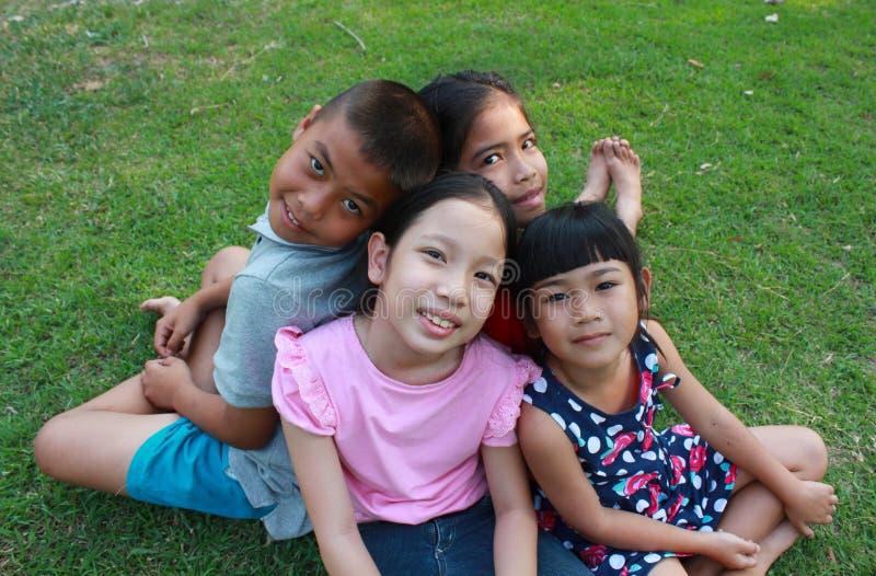 Fyra barn som spelar i parkera arkivbild