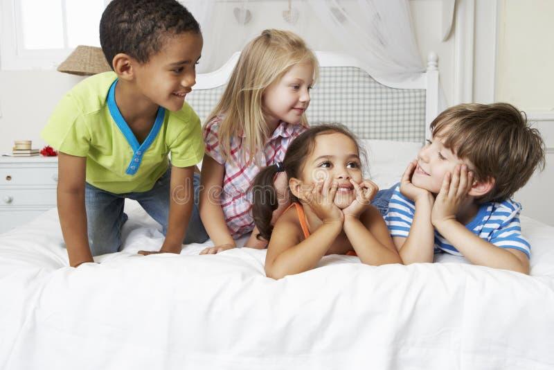 Fyra barn som spelar på säng tillsammans royaltyfri bild