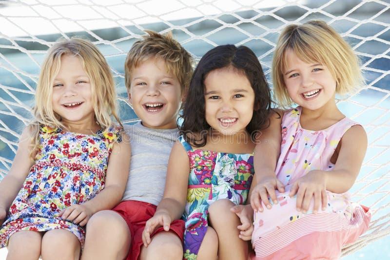 Fyra barn som tillsammans kopplar av i trädgårds- hängmatta arkivbild