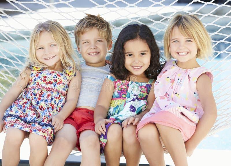 Fyra barn som tillsammans kopplar av i trädgårds- hängmatta arkivbilder