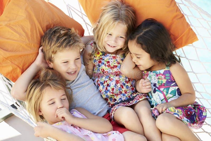 Fyra barn som tillsammans kopplar av i trädgårds- hängmatta fotografering för bildbyråer