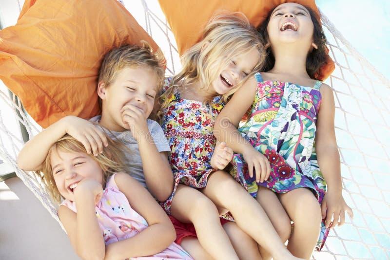 Fyra barn som tillsammans kopplar av i trädgårds- hängmatta arkivfoto