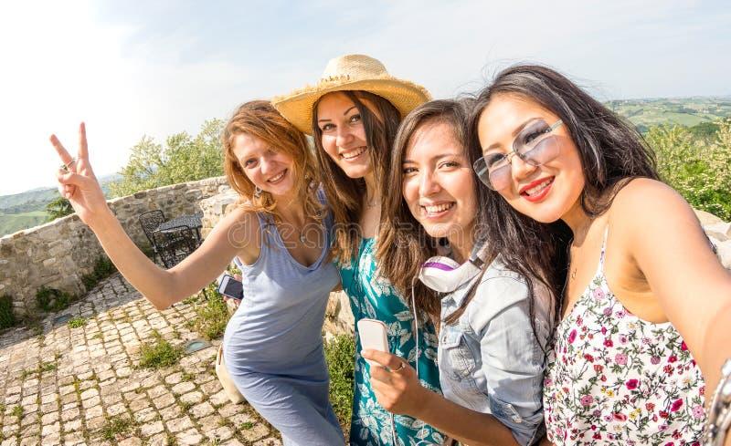 Fyra blandras- millennial flickvänner som tar selfie på landssidoutfärden - lyckliga flickor som har gyckel runt om gamla stadgat royaltyfri fotografi