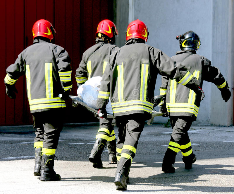Fyra brandmän i handling bär en bår arkivbild