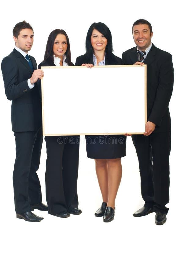 Fyra businesspeople med banret arkivfoto