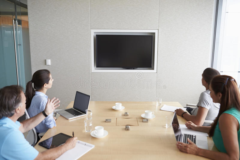 Fyra Businesspeople som har videokonferens i styrelse royaltyfri fotografi