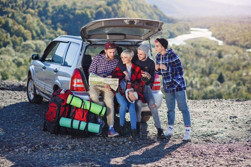 Fyra caucasian vänner som har, vilar efter lång tur, medan sitta i stammen av bilen, hällande te för ung kvinna från royaltyfria bilder