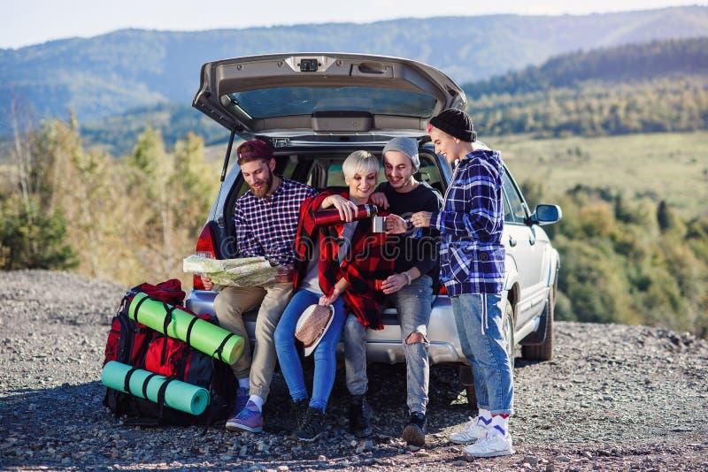 Fyra caucasian vänner som har, vilar efter lång tur, medan sitta i stammen av bilen, hällande te för ung kvinna från fotografering för bildbyråer
