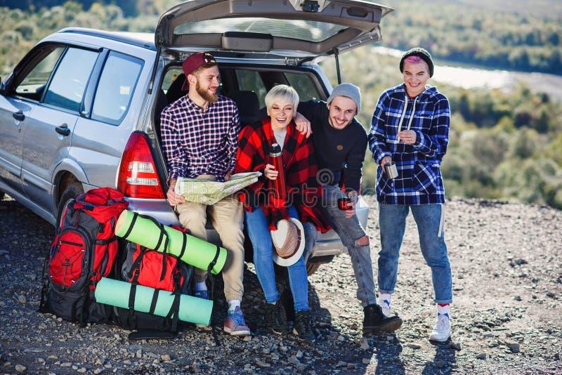 Fyra caucasian vänner som har, vilar efter lång tur, medan sitta i stammen av bilen, hällande te för ung kvinna från arkivbild