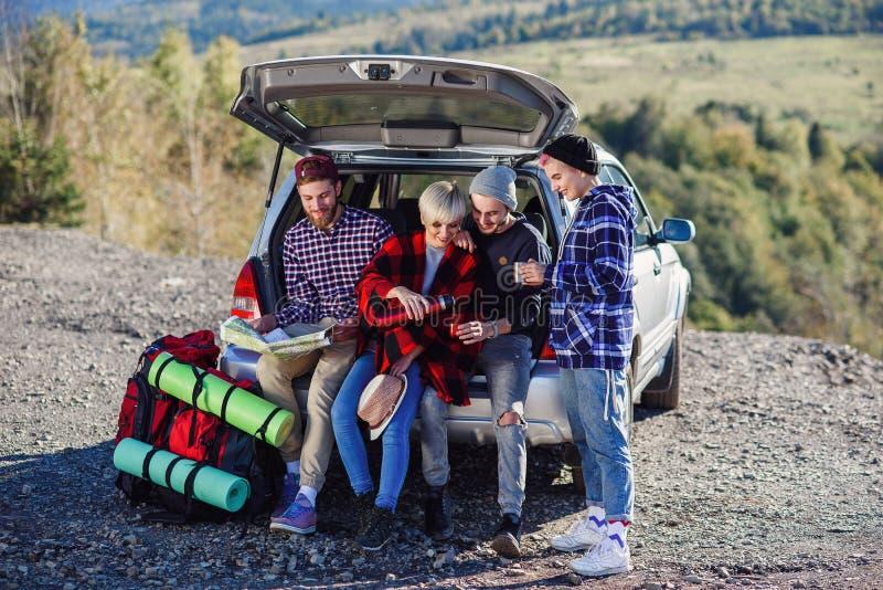 Fyra caucasian vänner som har, vilar efter lång tur, medan sitta i stammen av bilen, hällande te för ung kvinna från arkivfoton
