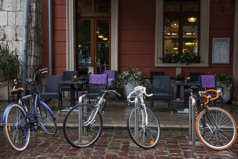 Fyra cyklar som parkeras på framdelen av kafét i regnet arkivfoton