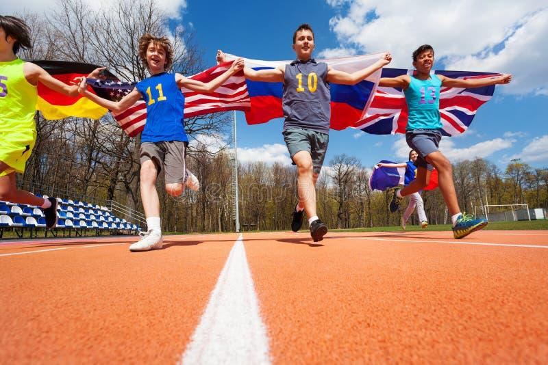 Fyra deltagare av internationellt lopp med flaggor fotografering för bildbyråer