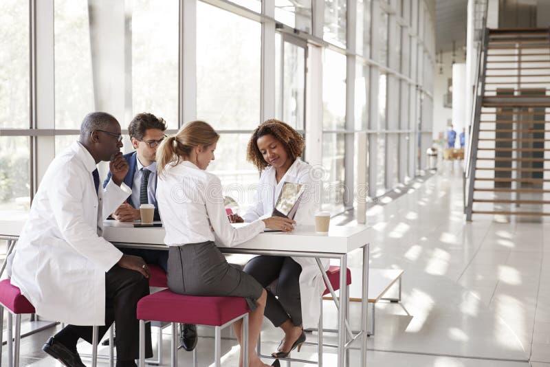 Fyra doktorer som ser bärbara datorn i en modern sjukhuslobby royaltyfri fotografi