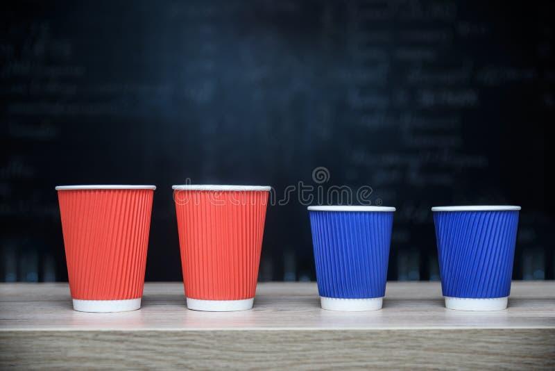 Fyra engångs- pappers- koppar för kaffe, trästångräknare, mörk mjuk bakgrund med att markera mitten och kopia gör mellanslag, pla royaltyfri bild