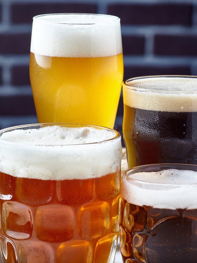 Fyra exponeringsglas med öl av olika färger royaltyfria foton