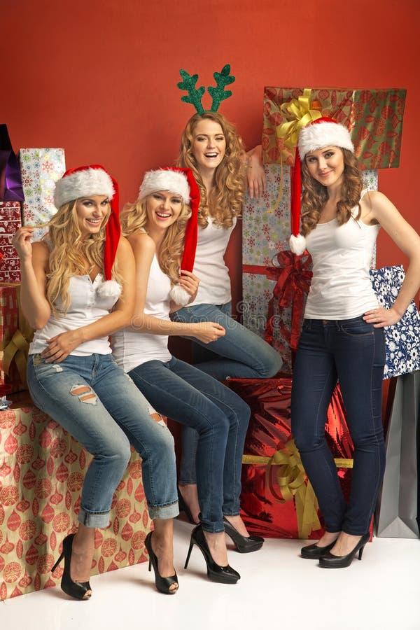 Fyra förföriska flickor som främjar julen arkivbilder