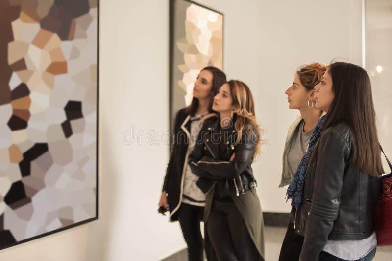 Fyra flickavänner som ser modern målning i konstgalleri arkivbild