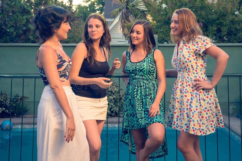Fyra flickavänner som ut hänger på pölen arkivbilder