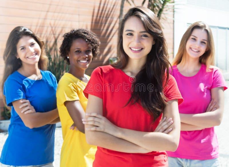 Fyra flickvänner med färgrika skjortor i staden royaltyfria bilder