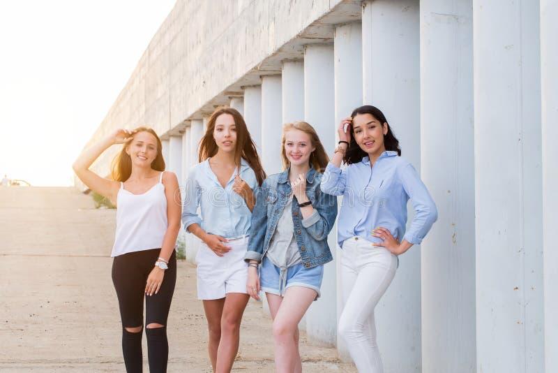 Fyra flickvänner som tillsammans ser kameran folk livsstil, kamratskap, kallbegrepp arkivfoton